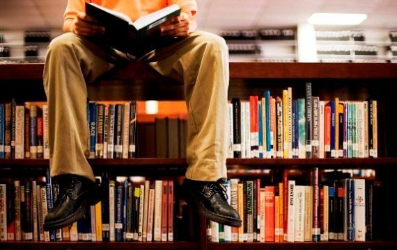 Man Reading Book and Sitting on Bookshelf in Library --- Image by © Royalty-Free/Corbis