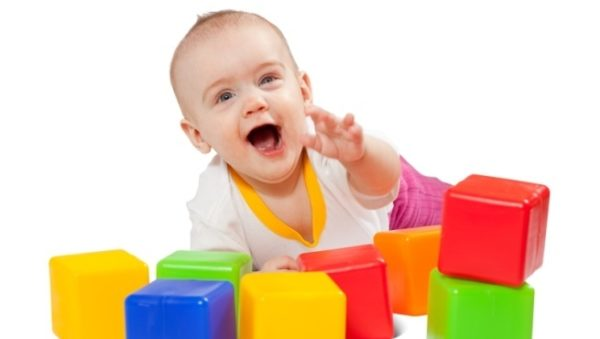 Happy baby plays  with toy blocks