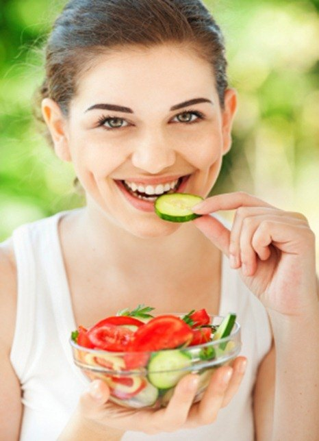 Beautiful young woman eating healthy salad