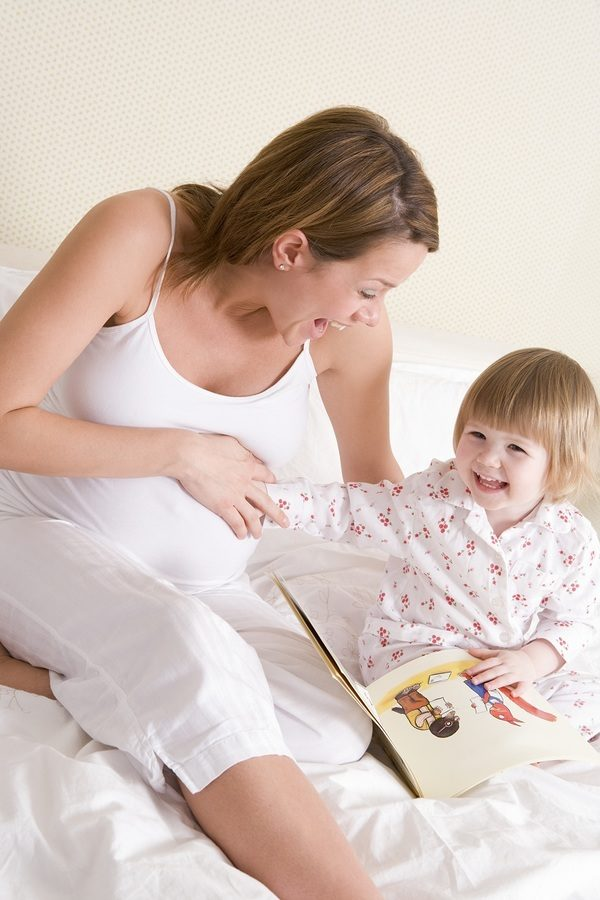 Pregnant woman in bedroom reading book with daughter laughing